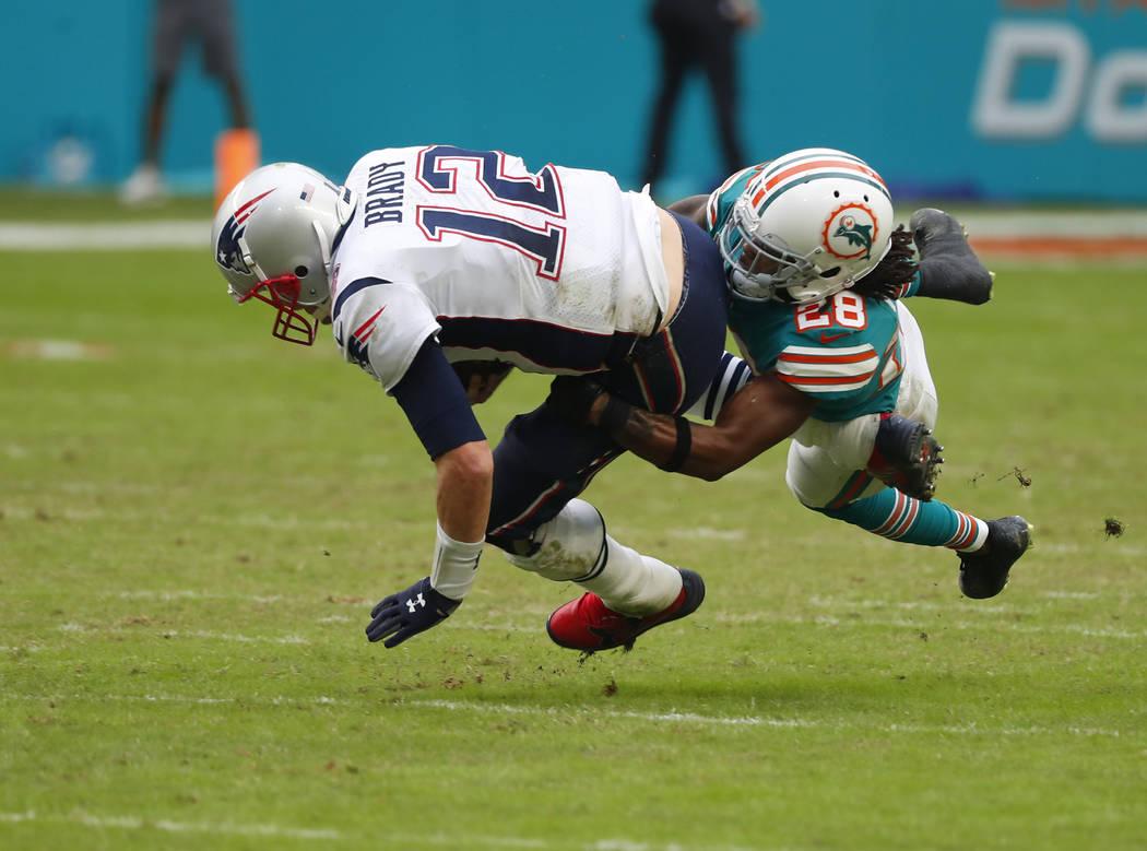 Miami Dolphins cornerback Bobby McCain (28) sacks New England Patriots quarterback Tom Brady (12), during the second half of an NFL football game, Sunday, Dec. 9, 2018, in Miami Gardens, Fla. (AP ...