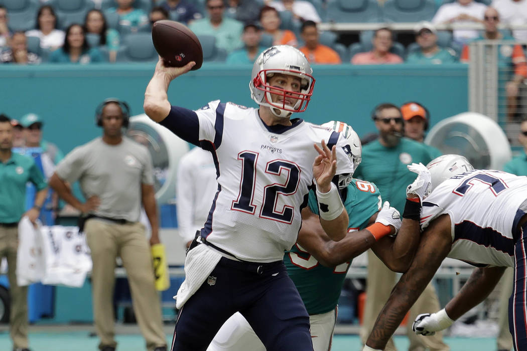 New England Patriots quarterback Tom Brady (12) looks to pass, during the first half of an NFL football game against the Miami Dolphins, Sunday, Dec. 9, 2018, in Miami Gardens, Fla. (AP Photo/Lynn ...