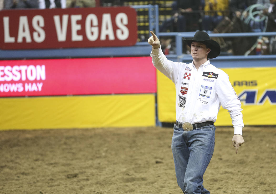Ty Erickson of Helena, Mont. (59) points to the crowd after competing in the steer wrestling event during the ninth go-round of the National Finals Rodeo at the Thomas & Mack Center in Las Veg ...
