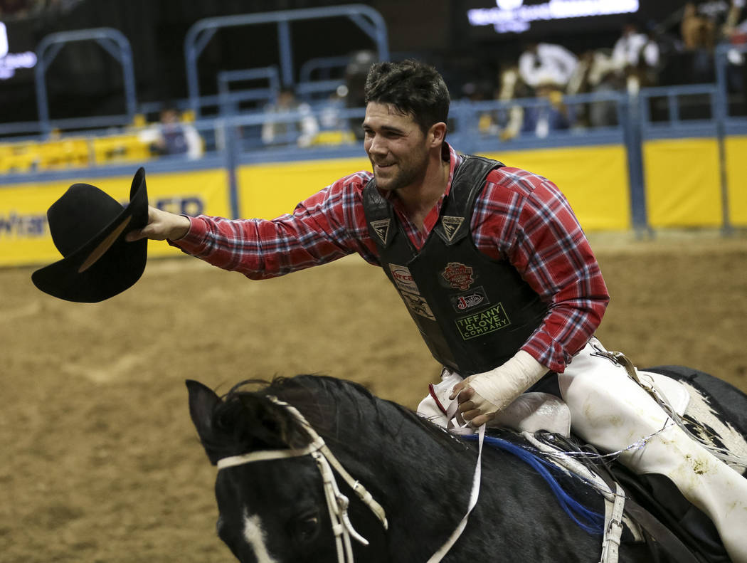 Eli Vastbinder of Union Grove, N.C. (105) takes a victory lap after taking the best score in the bull riding event during the ninth go-round of the National Finals Rodeo at the Thomas & Mack C ...