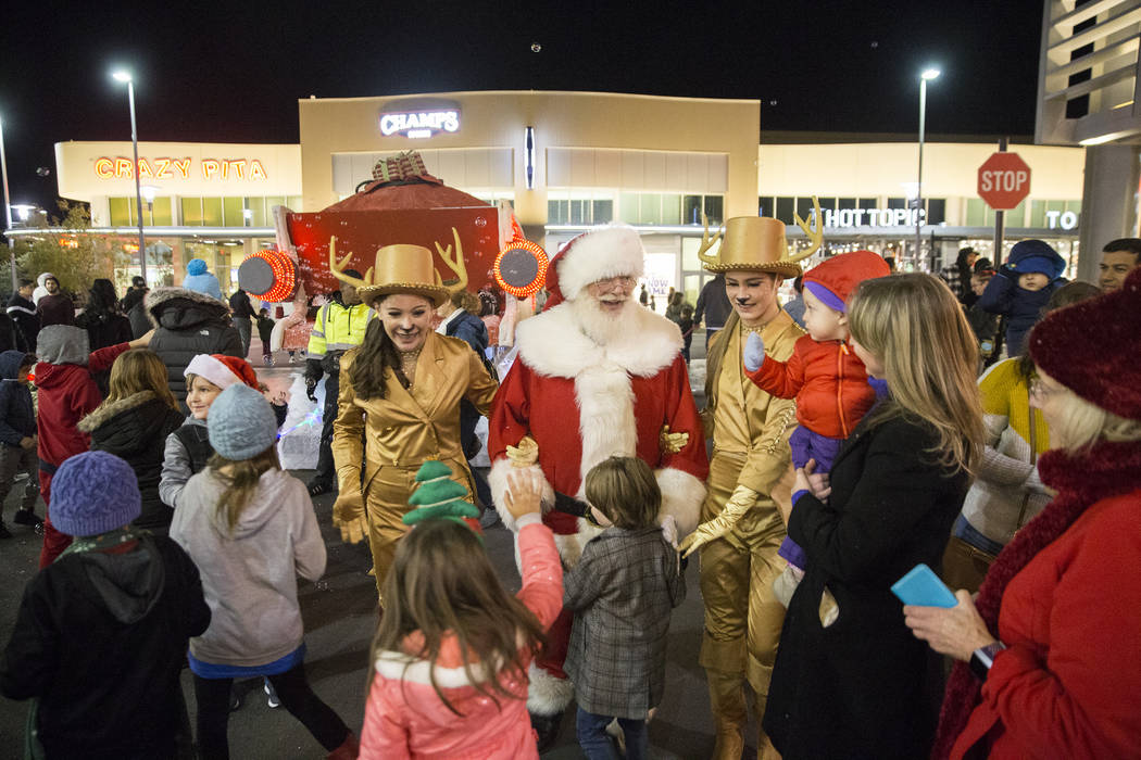 Santa is greeted by children as he walks down Festival Plaza Drive during the Downtown Summerlin Holiday Parade on Friday, Dec. 14, 2018, in Las Vegas. The parade features floats, dancers and fest ...