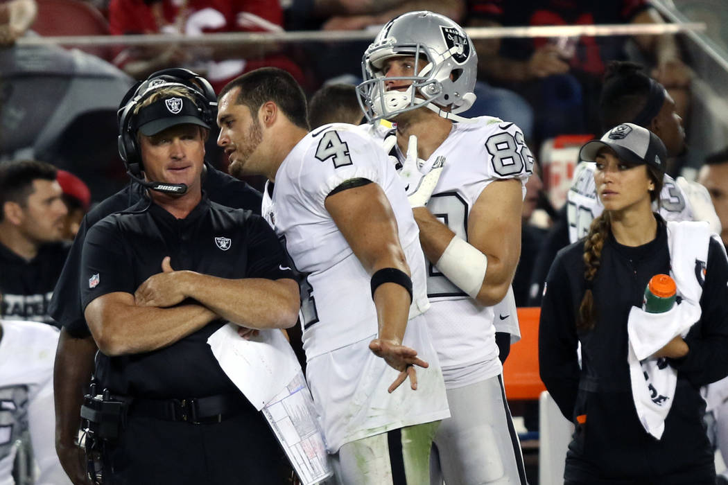 Oakland Raiders quarterback Derek Carr (4) speaks to head coach Jon Gruden after being benched in the fourth quarter as wide receiver Jordy Nelson (82) looks on during their NFL game against the S ...
