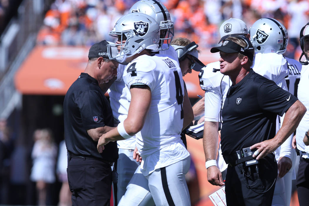 Oakland Raiders head coach Jon Gruden gives instruction to quarterback Derek Carr (4) during the first half of their NFL game against the Denver Broncos in Denver, Colo., Sunday, Sept. 16, 2018. H ...