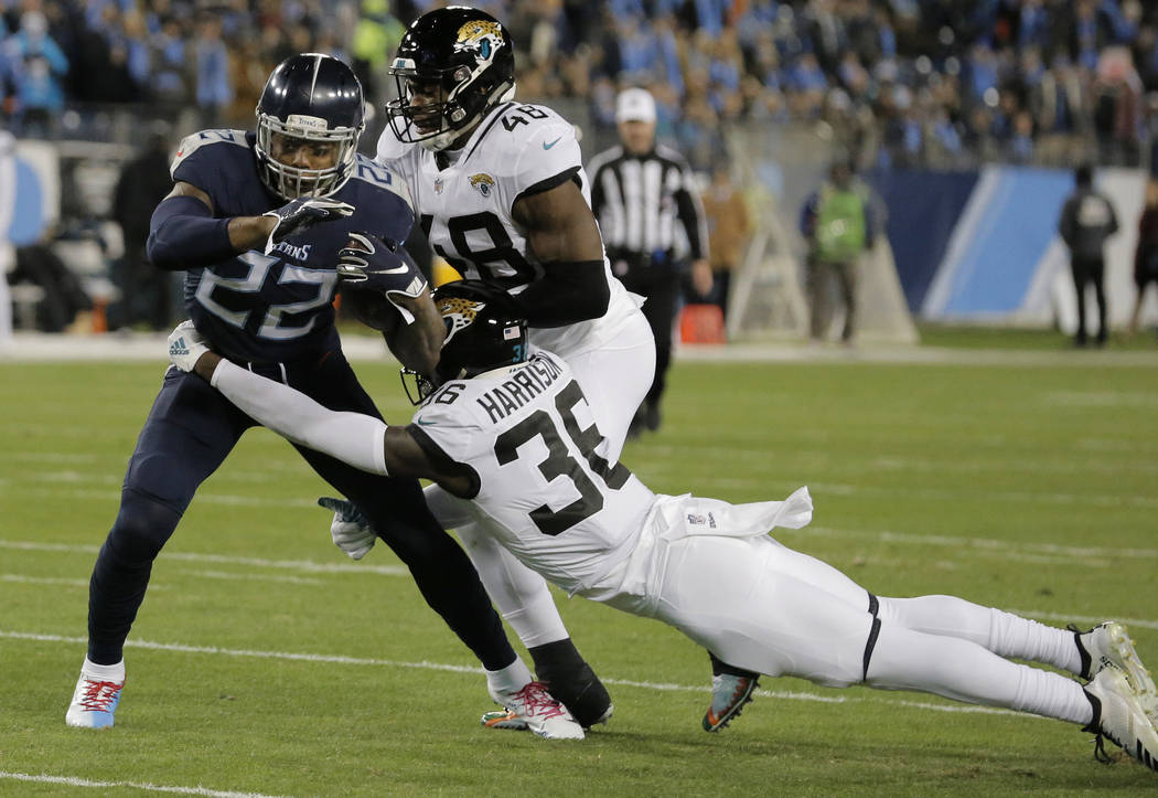 Tennessee Titans running back Derrick Henry (22) breaks a tackle by Jacksonville Jaguars defensive back Ronnie Harrison (36) during the first half of an NFL football game, Thursday, Dec. 6, 2018, ...