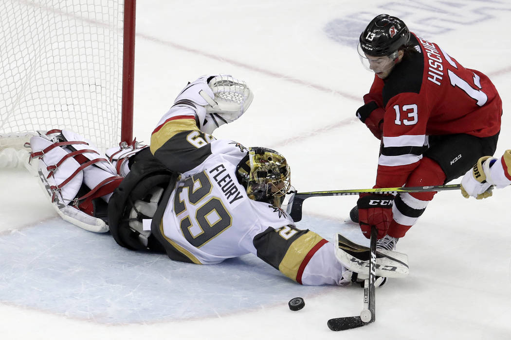 New Jersey Devils center Nico Hischier (13), of Switzerland, prepares to score the game-winning goal on Vegas Golden Knights goaltender Marc-Andre Fleury (29) during overtime in an NHL hockey game ...