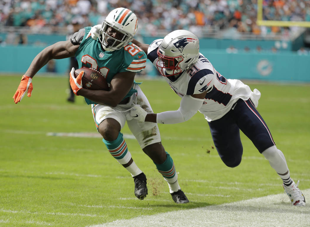 New England Patriots strong safety Duron Harmon (21) tackles Miami Dolphins running back Frank Gore (21), during the first half of an NFL football game, Sunday, Dec. 9, 2018, in Miami Gardens, Fla ...