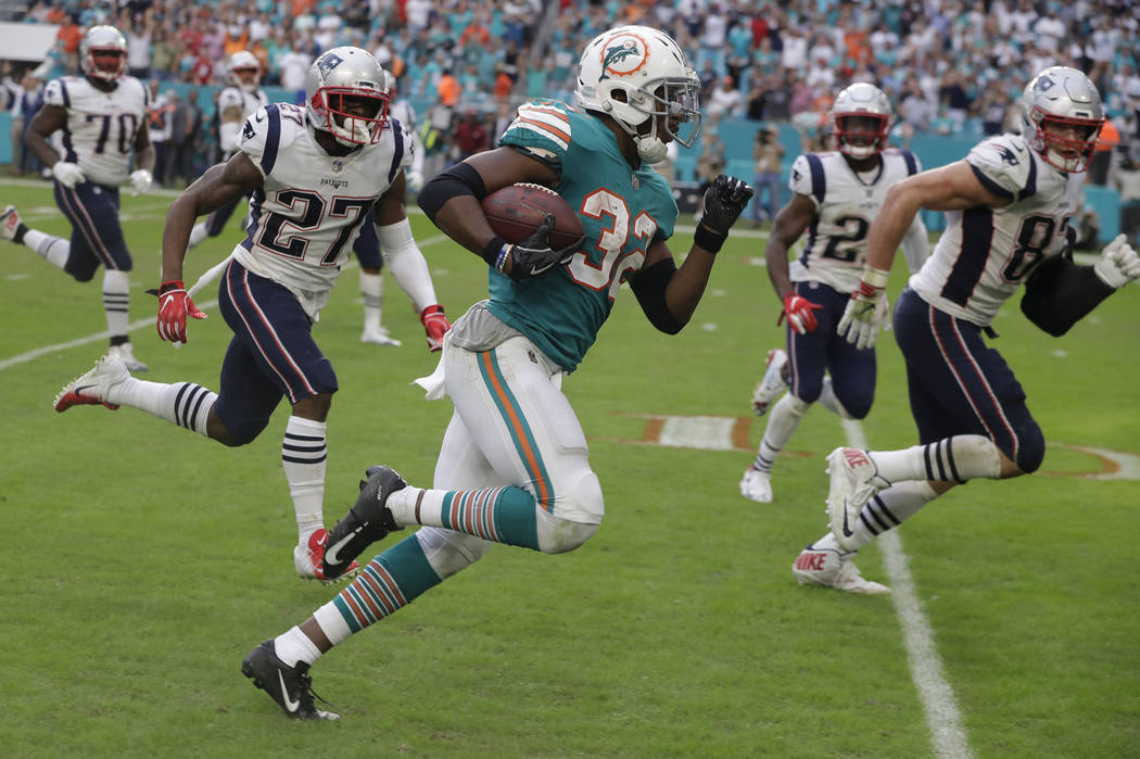 FILE - In this Dec. 9, 2018, file photo, Miami Dolphins running back Kenyan Drake (32) runs for a touchdown during the second half of an NFL football game against the New England Patriots, in Miam ...