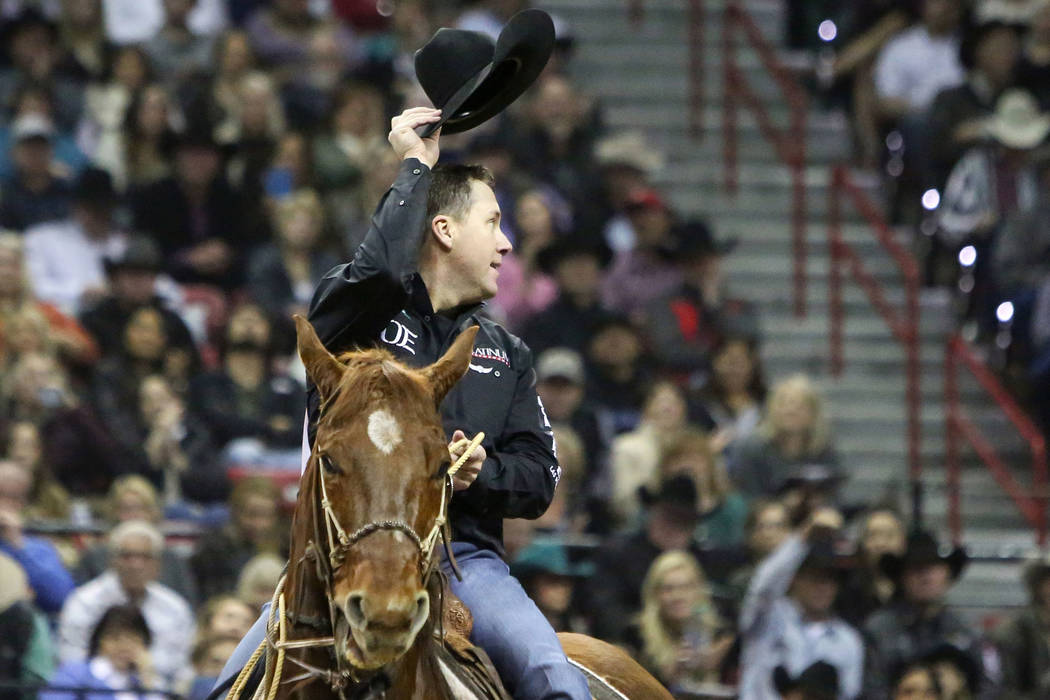 Trevor Brazile of Decatur, Texas (2) tips his hat after competing in tie-down roping during the tenth go-round of the National Finals Rodeo at the Thomas & Mack Center in Las Vegas, Saturday, ...