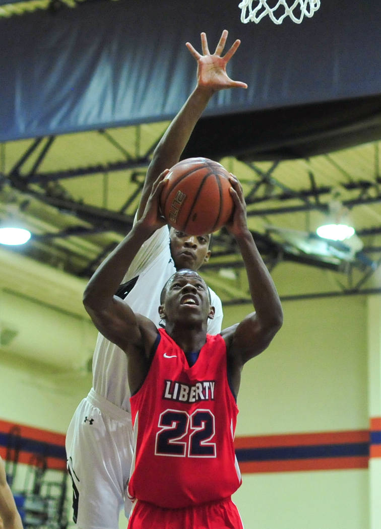 Faith Lutheran's Azavier Johnson (5) blocks a shot from Liberty's Jordan Wafer (22) during a game between Liberty High School and Faith Lutheran at Bishop Gorman High School in Las Vegas on Saturd ...
