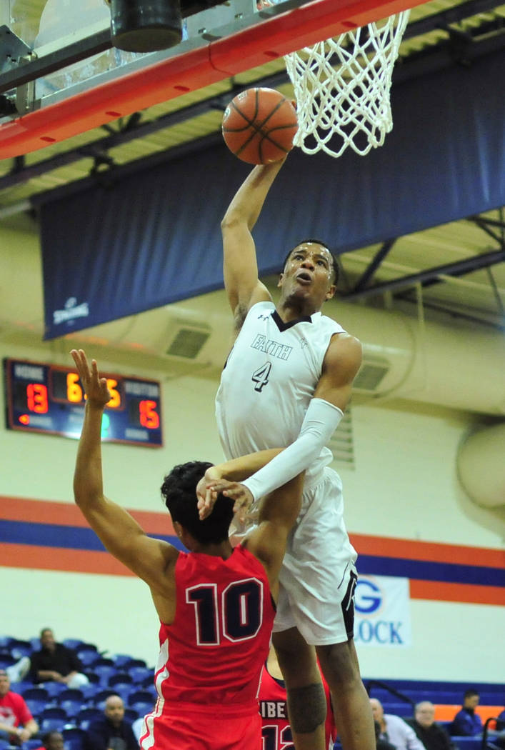 Faith Lutheran's Sedrick Hammond (4) goes for a dunk over Liberty's Lehi Ausage (10) during a game between Liberty High School and Faith Lutheran at Bishop Gorman High School in Las Vegas on Satur ...