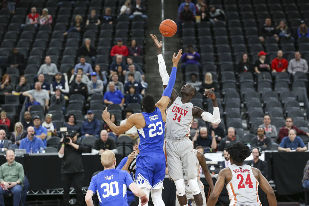 Brigham Young Cougars forward Yoeli Childs (23) and UNLV Rebels forward Cheikh Mbacke Diong (34) tip off to start the first half of an NCAA college basketball game at T-Mobile Arena in Las Vegas o ...
