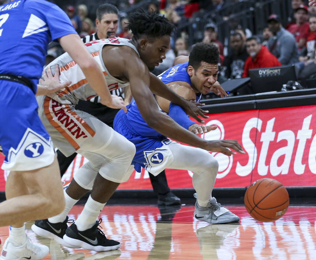 UNLV Rebels forward Joel Ntambwe (24) and Brigham Young Cougars forward Yoeli Childs (23) vie for a loose ball during the first half of an NCAA college basketball game at T-Mobile Arena in Las Ve ...