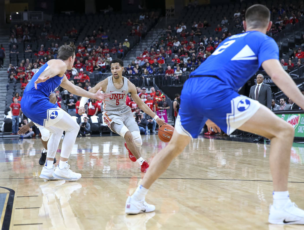UNLV Rebels guard Noah Robotham (5) dribbles the ball against Brigham Young defenders during the first half of an NCAA college basketball game at T-Mobile Arena in Las Vegas on Saturday, Dec. 15, ...