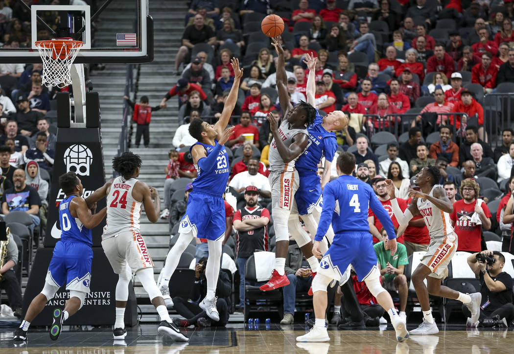 UNLV Rebels forward Jonathan Tchamwa Tchatchoua (30) takes a shot between Brigham Young Cougars forward Yoeli Childs (23) and Cougars guard TJ Haws (30) during the second half of an NCAA college b ...