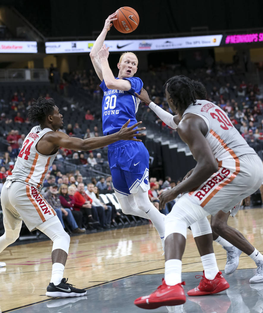Brigham Young Cougars guard TJ Haws (30) passes the ball as UNLV Rebels forwards Joel Ntambwe (24) and Jonathan Tchamwa Tchatchoua (30) defend the court during the second half of an NCAA college b ...