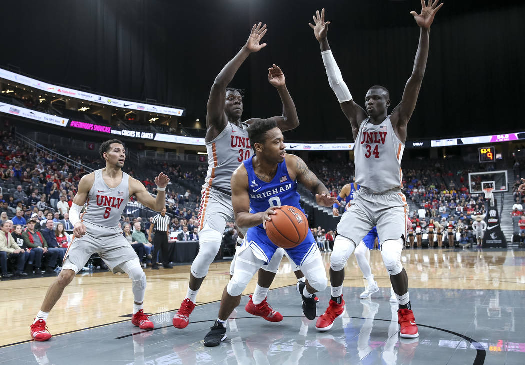 Brigham Young Cougars guard Jahshire Hardnett (0) is pressured by UNLV Rebels forwards Jonathan Tchamwa Tchatchoua (30) and Cheikh Mbacke Diong (34) during the second half of an NCAA college baske ...