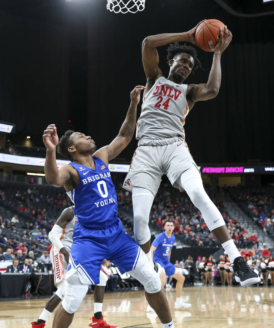 UNLV Rebels forward Joel Ntambwe (24) pulls in the rebound over Brigham Young Cougars guard Jahshire Hardnett (0) during the second half of an NCAA college basketball game at T-Mobile Arena in Las ...