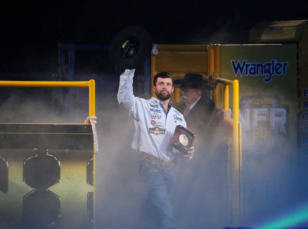 Paul Eaves of Lonedell, Mo. (23) walks up to be honored on stage after winning the Team Roping category during the tenth go-round of the National Finals Rodeo at the Thomas & Mack Center in La ...