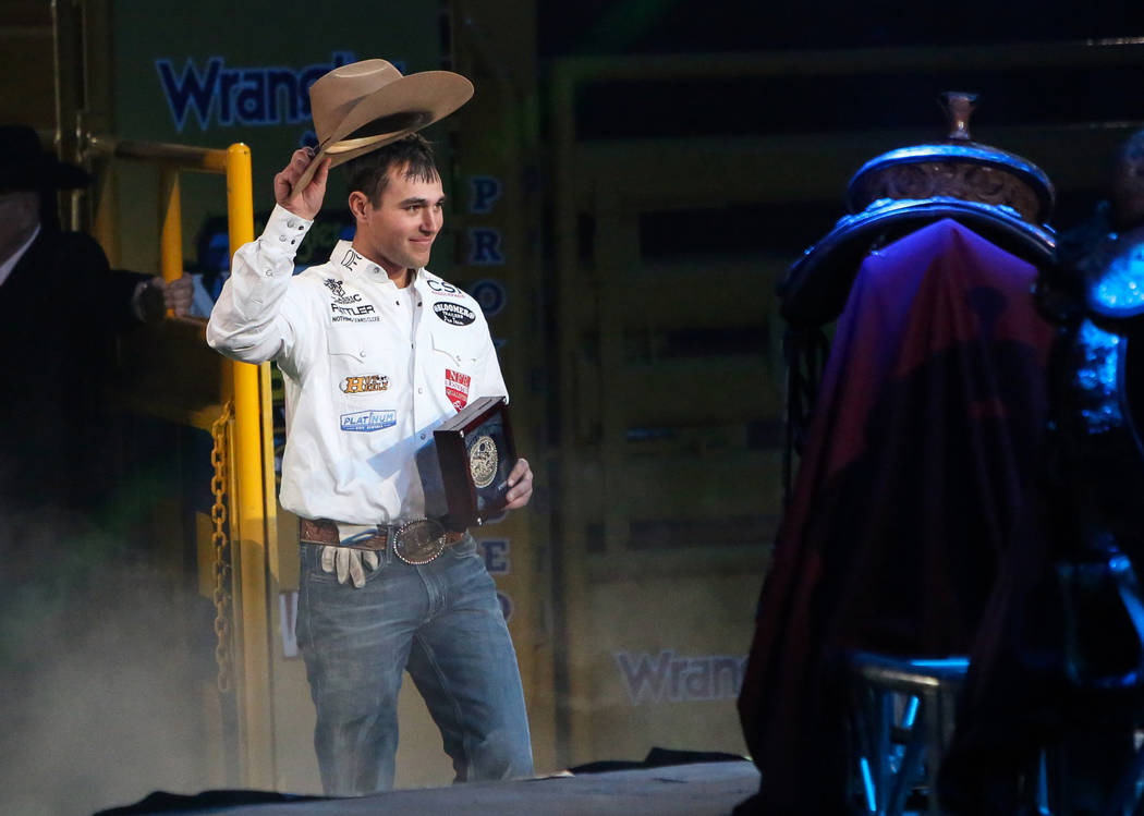 Clay Smith of Broken Bow, Okla. (22) walks up to be honored on stage after winning the Team Roping category during the tenth go-round of the National Finals Rodeo at the Thomas & Mack Center i ...