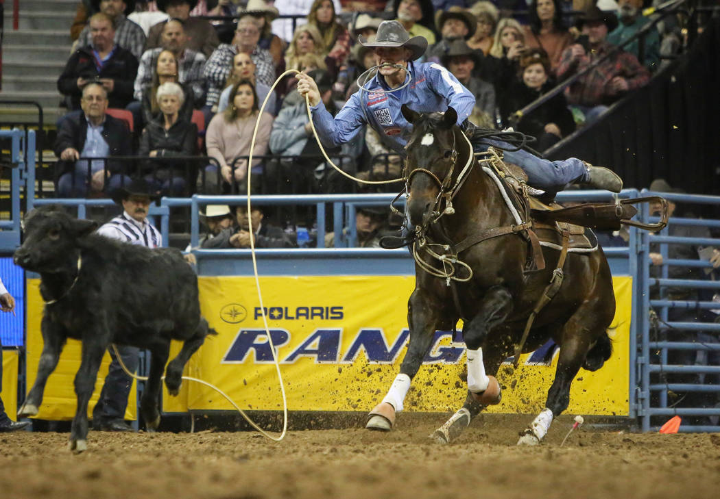 Tuf Cooper of Decatur, Texas (1) competes in tie-down roping during the tenth go-round of the National Finals Rodeo at the Thomas & Mack Center in Las Vegas, Saturday, Dec. 15, 2018. Caroline ...