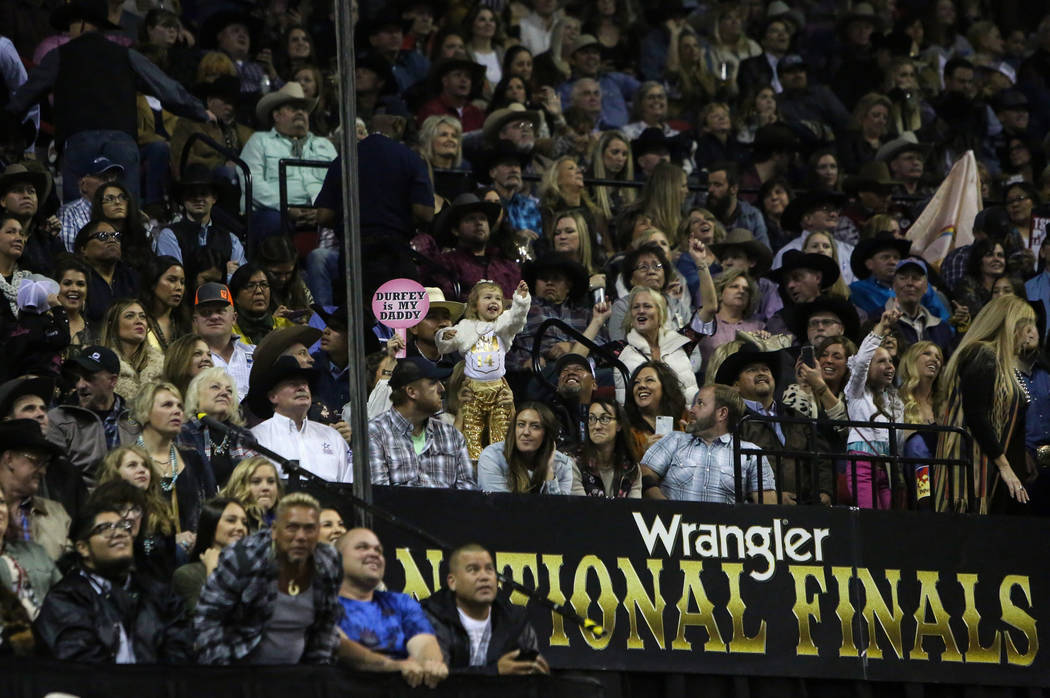 The Durfey family cheers on Tyson Durfey of Weatherford, Texas (14) before he competes in tie-down roping during the tenth go-round of the National Finals Rodeo at the Thomas & Mack Center in ...