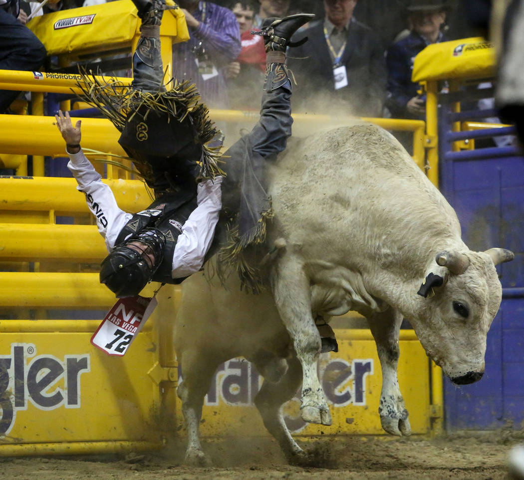 """Dustin Boquet of Bourg, La. (72) rides """"Thunder Rolls"""" while competing bull riding during the tenth go-round of the National Finals Rodeo at the Thomas & Mack Center in Las Vegas, Sa ..."""