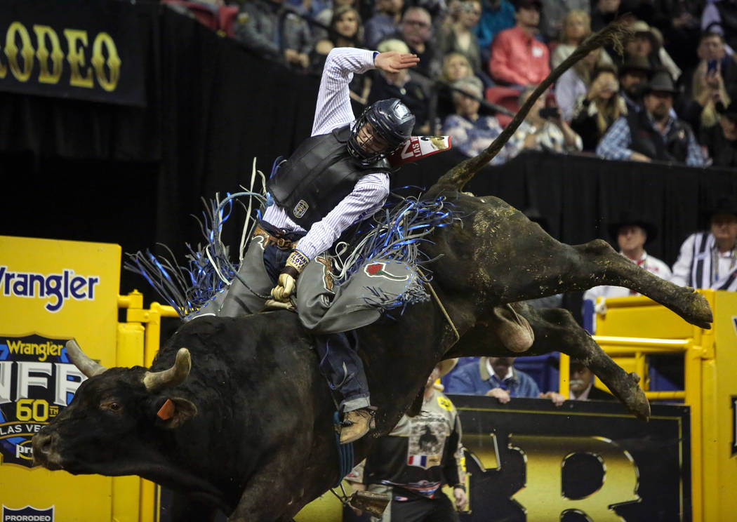 """Chase Dougherty of Canby, Ore. (36) rides """"Wall Cloud"""" while competing in bull riding during the tenth go-round of the National Finals Rodeo at the Thomas & Mack Center in Las Vegas, ..."""