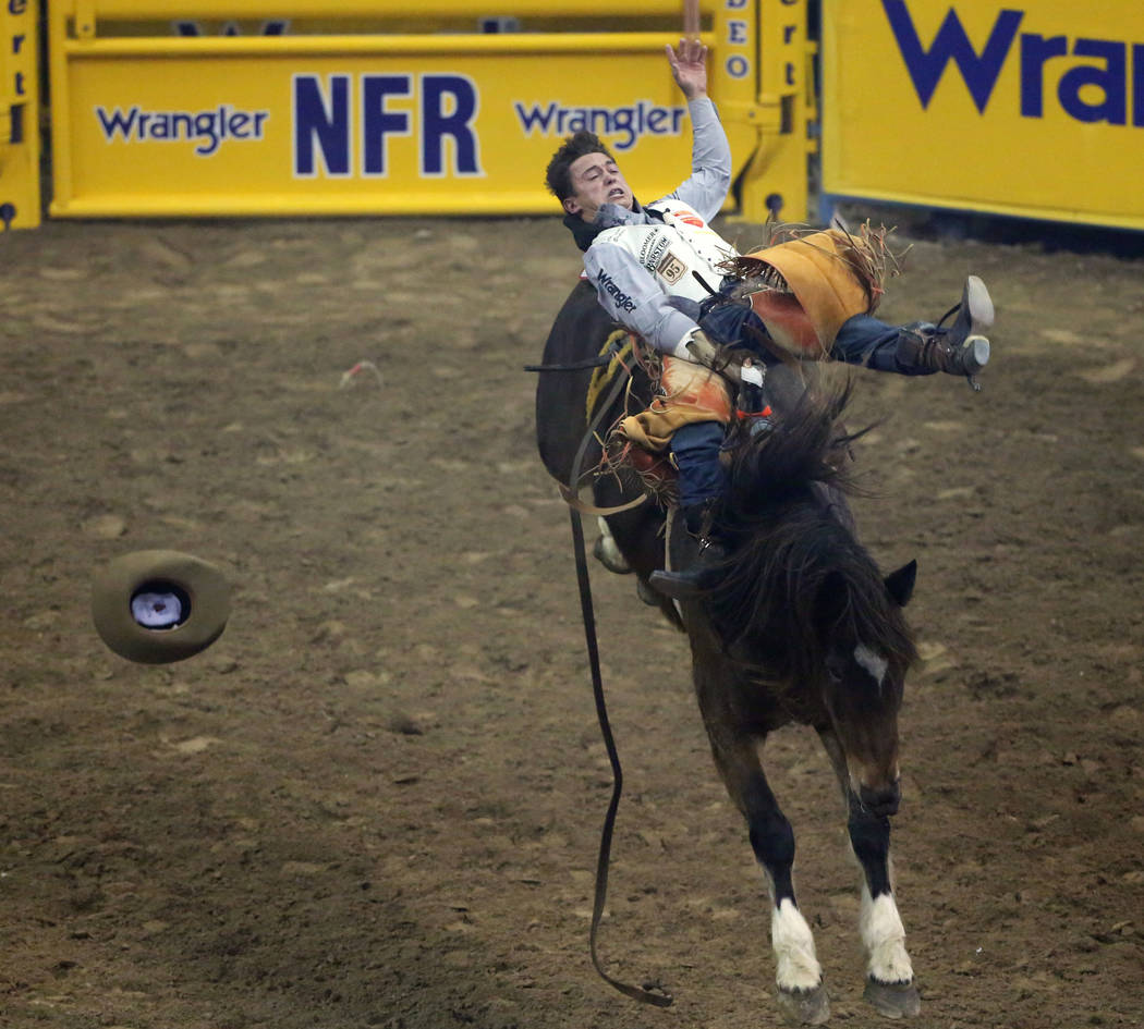 """Clayton Biglow of Clements, Calif. (10) rides """"Top Flight"""" while competing in bareback riding during the tenth go-round of the National Finals Rodeo at the Thomas & Mack Center in La ..."""