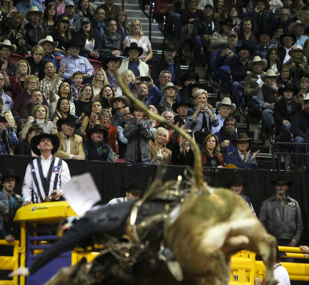 """Attendees watch Sage Kimzey of Strong City, Okla. (3) ride """"Shootin' Stars"""" as he competes in bull riding during the tenth go-round of the National Finals Rodeo at the Thomas & Mack ..."""