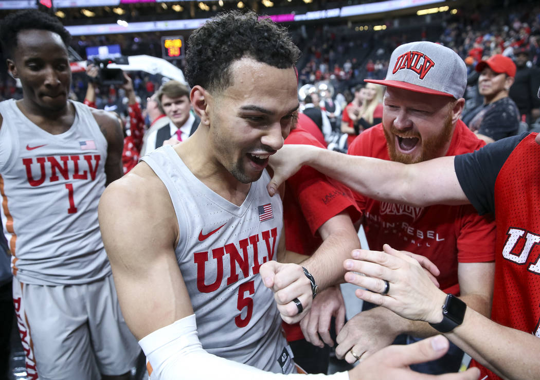 UNLV Rebels guard Noah Robotham (5) is congratulated by fans as he leaves the court after scoring the game-winning shot to defeat the Brigham Young Cougars 92-90 following an NCAA college basketba ...