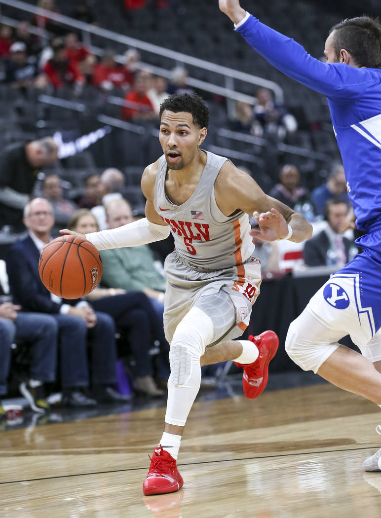 UNLV Rebels guard Noah Robotham (5) dribbles the ball past Brigham Young Cougars guard Nick Emery (4) during the first half of an NCAA college basketball game at T-Mobile Arena in Las Vegas on Sat ...