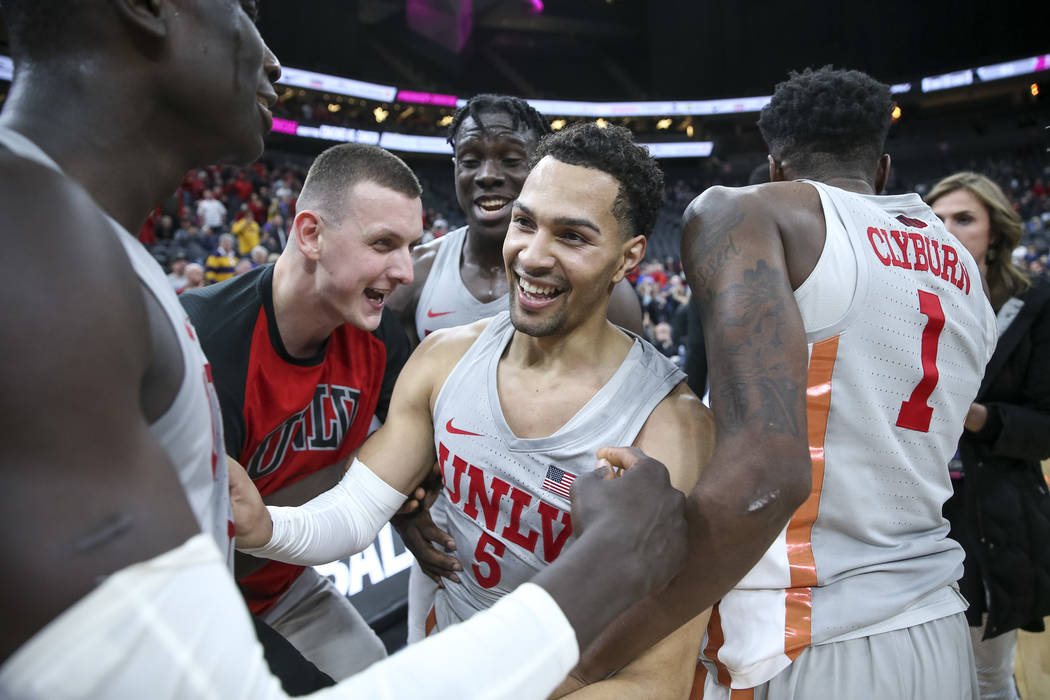 UNLV Rebels guard Noah Robotham (5) is congratulated by his teammates after scoring the game-winning shot to defeat the Brigham Young Cougars 92-90 following an NCAA college basketball game at T-M ...
