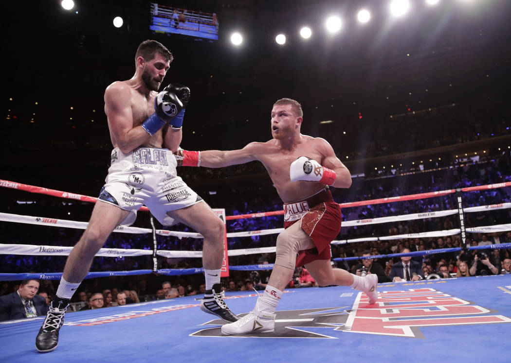 Mexico's Canelo Alvarez, right, punches England's Rocky Fielding during the second round of a WBA super middleweight championship boxing match Saturday, Dec. 15, 2018, in New York. Alvarez stopped ...