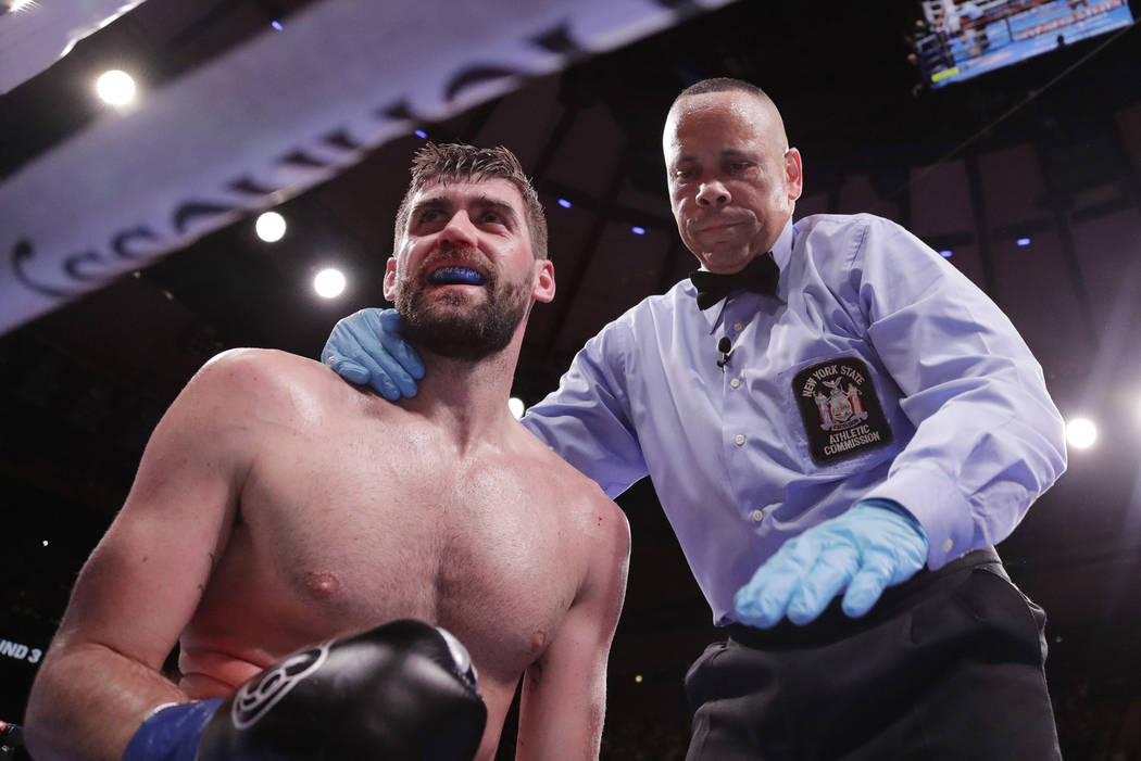 England's Rocky Fielding, left, reacts as the referee stops the fight after Mexico's Canelo Alvarez knocked him down during the third round of a WBA super middleweight championship boxing match Sa ...