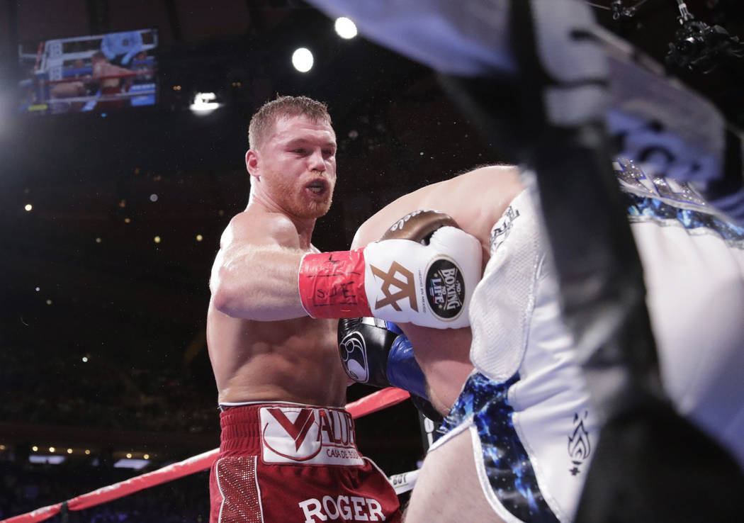 Mexico's Canelo Alvarez, left, punches England's Rocky Fielding during the third round of a WBA super middleweight championship boxing match Saturday, Dec. 15, 2018, in New York. Alvarez stopped F ...