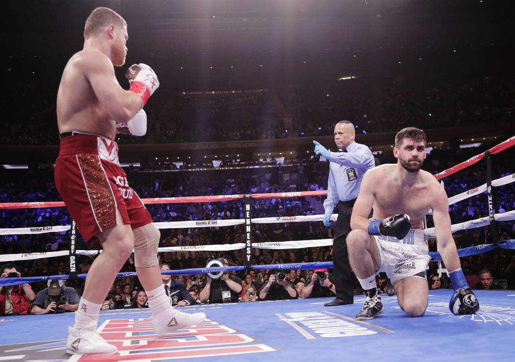 England's Rocky Fielding takes a knee after being knocked down by Mexico's Canelo Alvarez, left, during the first round of a WBA super middleweight championship boxing match Saturday, Dec. 15, 201 ...