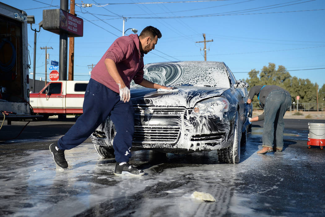 Joel Morales, a friend of Jonathan Garcia, who died Wednesday after falling outside Trump hotel, washes down a car during a carwash fundraiser in Las Vegas, Sunday, Dec. 16, 2018. Caroline Brehman ...
