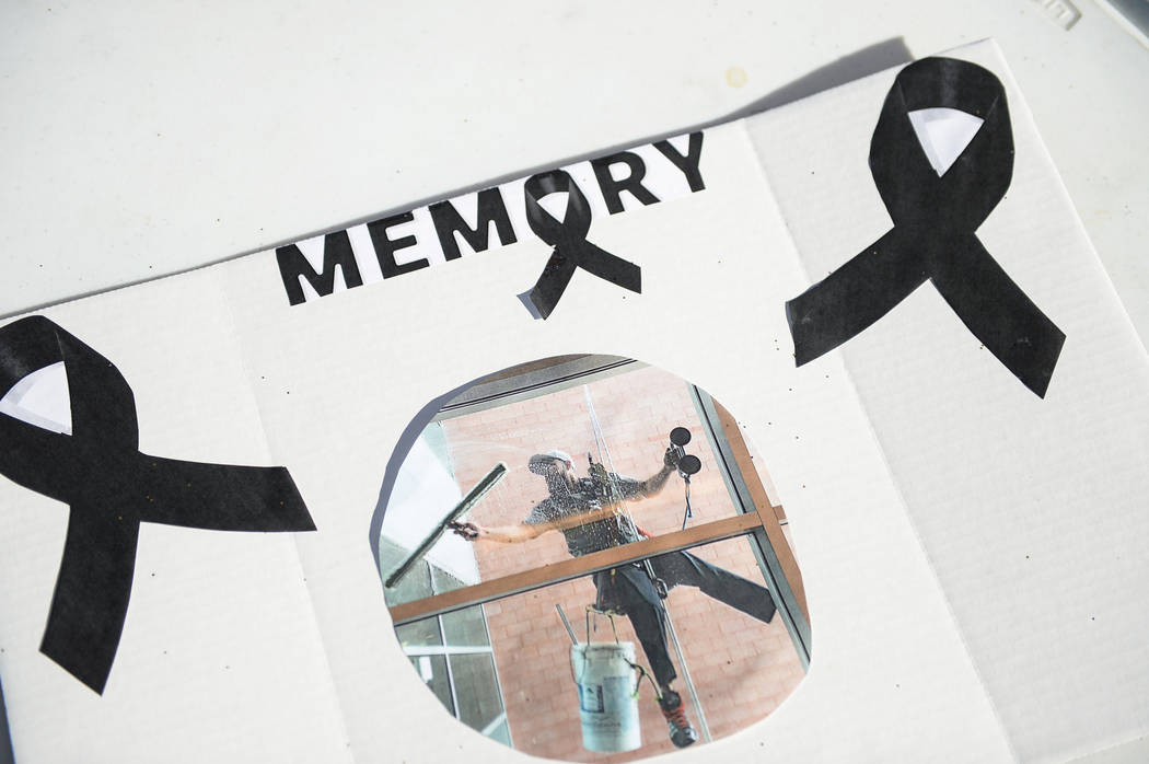 A sign with a photograph of Jonathan Garcia, who died Wednesday after falling outside Trump hotel, is displayed on a poster during a carwash fundraiser put on by his friends in Las Vegas, Sunday, ...