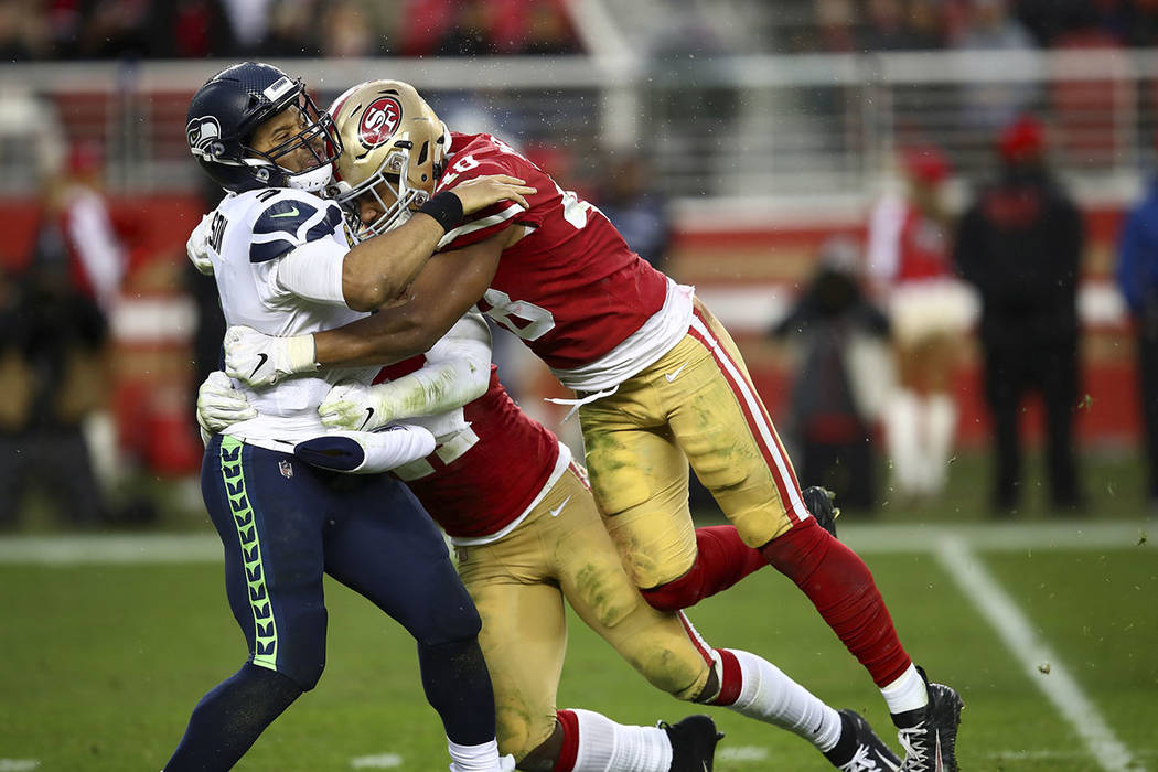 Seattle Seahawks quarterback Russell Wilson, left, is hit after passing by San Francisco 49ers linebacker Fred Warner, right, and linebacker Elijah Lee, bottom, during the second half of an NFL fo ...
