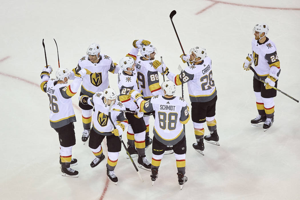 Vegas Golden Knights' Alex Tuch (89) top, celebrates with teammates after scoring a goal during overtime of an NHL hockey game against the New York Rangers, Sunday, Dec. 16, 2018, in New York. (AP ...