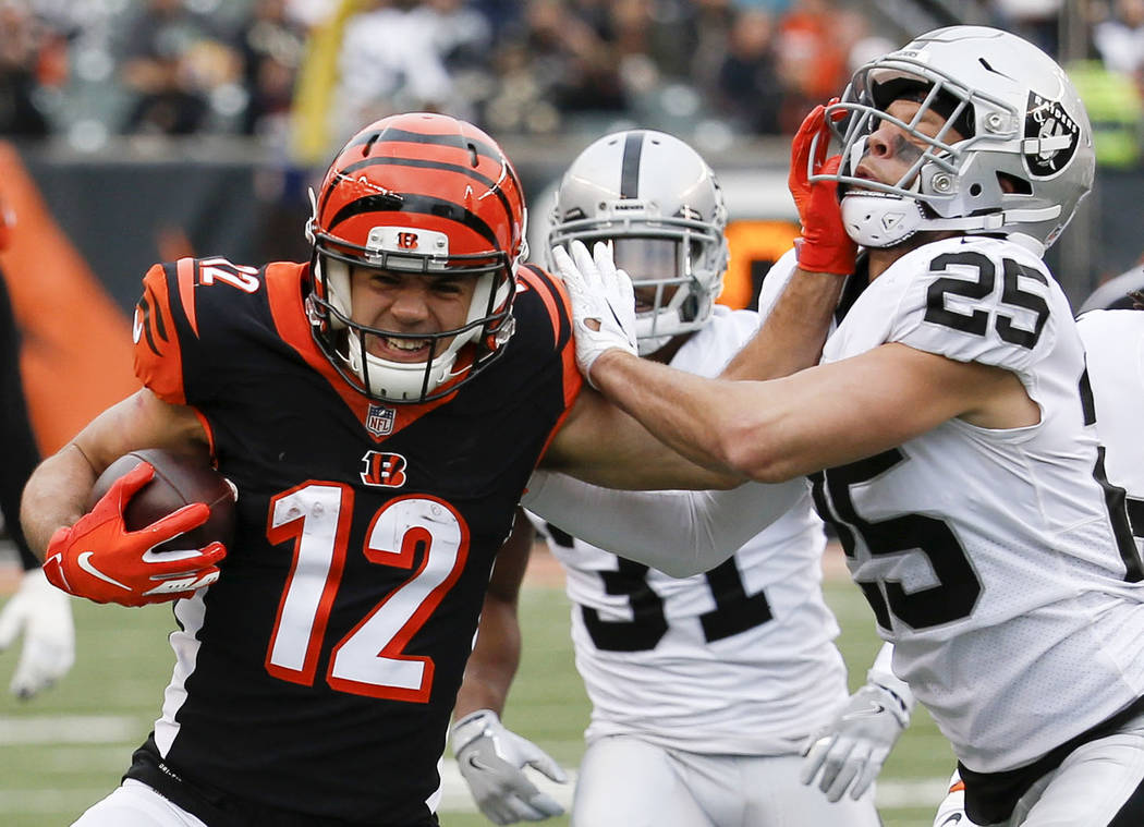 Cincinnati Bengals wide receiver Alex Erickson (12) runs the ball against Oakland Raiders free safety Erik Harris (25) in the second half of an NFL football game, Sunday, Dec. 16, 2018, in Cincinn ...