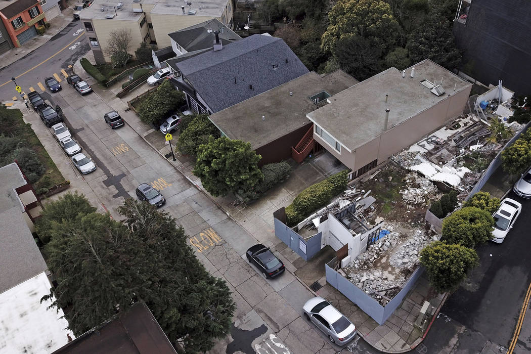 This Friday, Dec. 14, 2018, photo shows a demolished house, right, on a property in San Francisco. A man who illegally demolished the San Francisco house designed by the modernist architect Richar ...