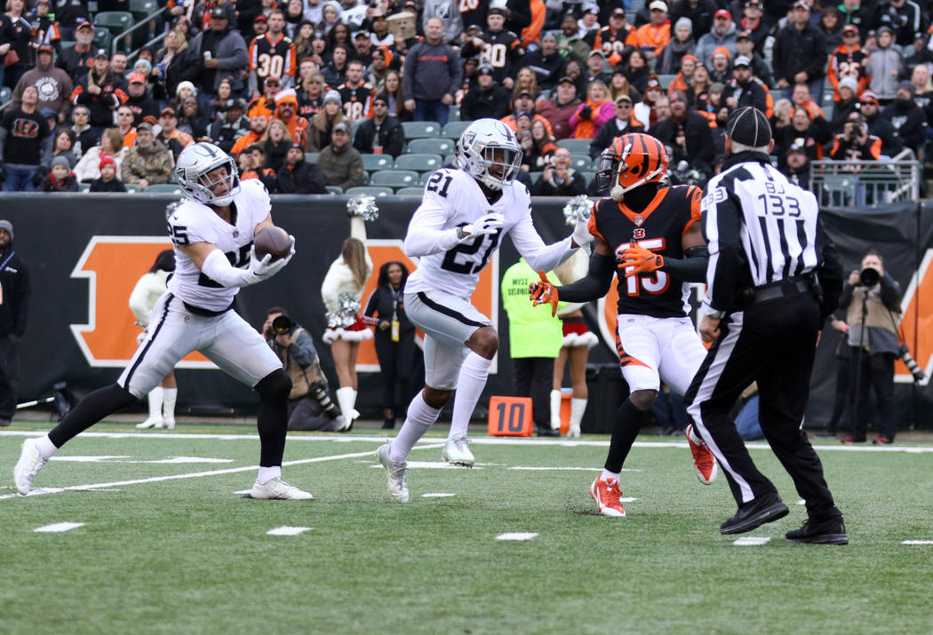 Oakland Raiders free safety Erik Harris (25) intercepts the football as cornerback Gareon Conley (21) moves to block Cincinnati Bengals wide receiver John Ross (15) during the first half of an NFL ...