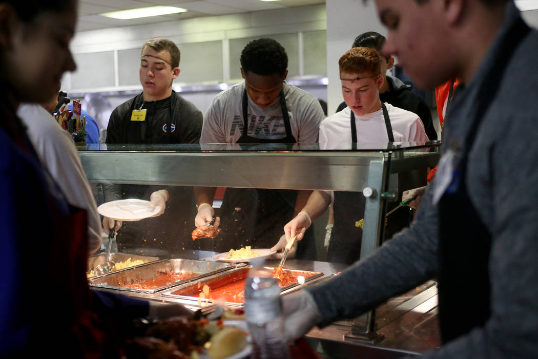 Michael Frailey, 15, from left, Camden Miller, 15, and Cameron Gray, 14, all students from the Bishop Gorman High School football team, serve food at the Christmas meal sponsored by the Frank and ...