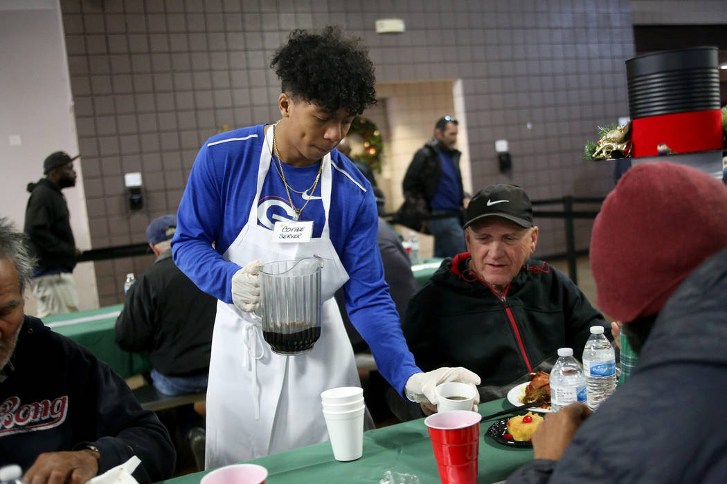 Jovani Hawkins, 17, serves coffee to Ismael Medina at the Christmas meal sponsored by the Frank and Victoria Fertitta Foundation, at Catholic Charities of Southern Nevada in Las Vegas, Sunday, Dec ...