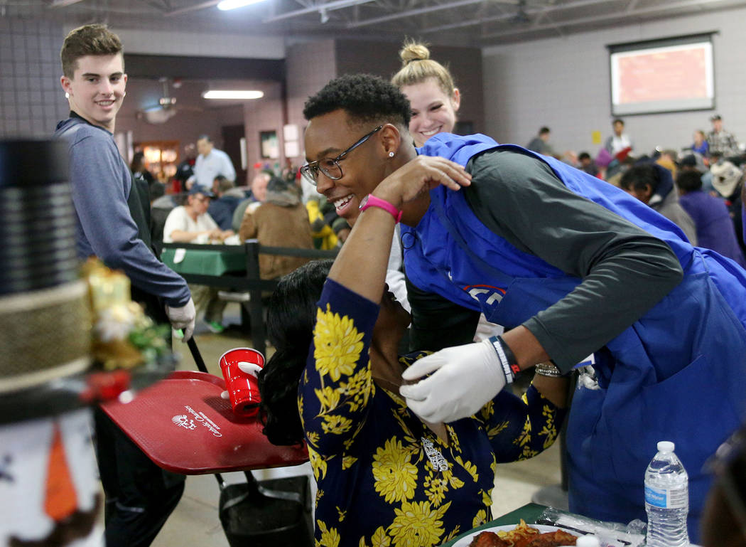 Volunteer Donovan Smith, 17, a Bishop Gorman football team member, hugs Laurice Adams, a guest, at the Christmas meal sponsored by the Frank and Victoria Fertitta Foundation, at Catholic Charities ...