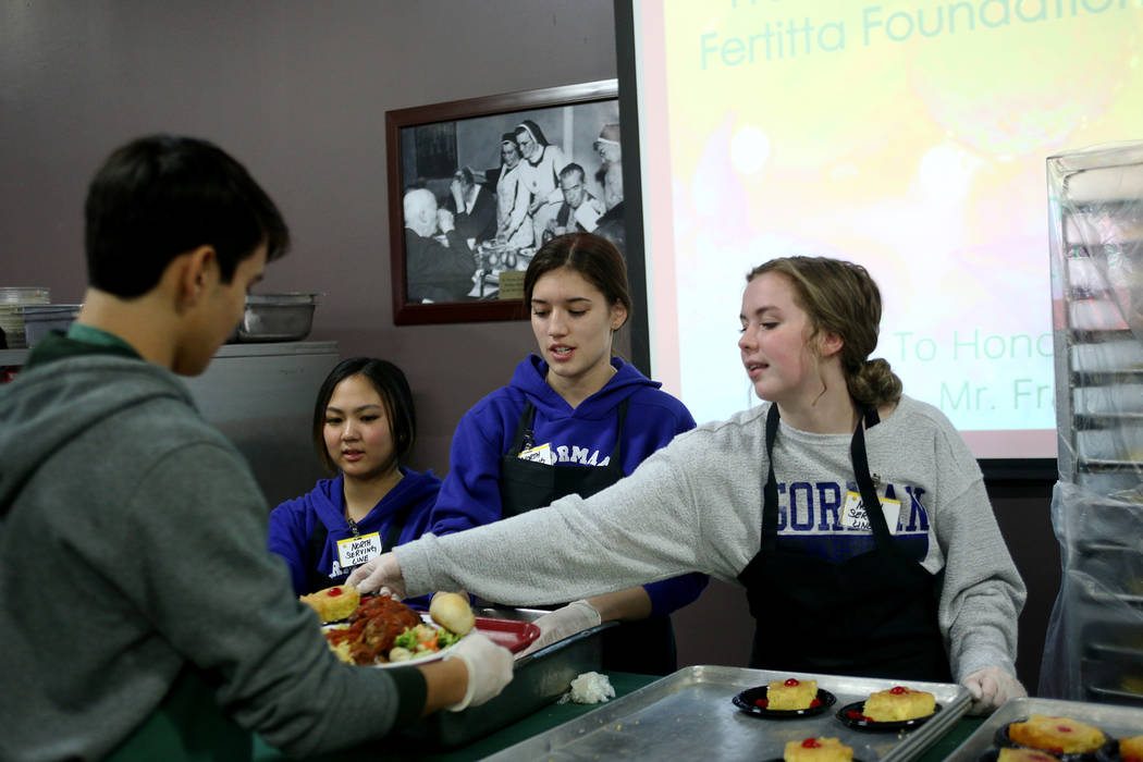 Kelly Hashiro, 17, from left, Keira Fincher, 15, and Haley Taylor, 17, serve dessert and bread at the Christmas meal sponsored by the Frank and Victoria Fertitta Foundation, at Catholic Charities ...