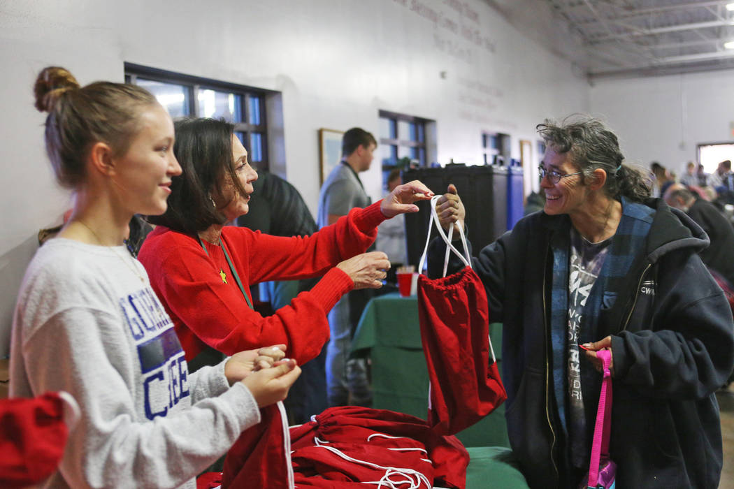 Sandee Tiberti hands a gift bag of toiletries, water and socks to Corey Gunter at the Christmas meal sponsored by the Frank and Victoria Fertitta Foundation, at Catholic Charities of Southern Neva ...