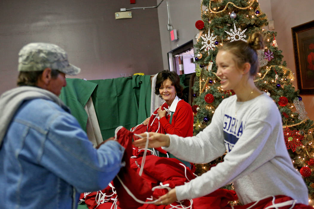 Victoria Fertitta looks on as Caroline Nielson, 17, hands a gift bag of toiletries, water and socks to a guest at the Christmas meal sponsored by the Frank and Victoria Fertitta Foundation, at Cat ...