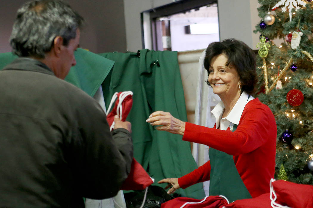 Victoria Fertitta hands a gift bag of toiletries, water and socks to a guest at the Christmas meal sponsored by the Frank and Victoria Fertitta Foundation, at Catholic Charities of Southern Nevada ...
